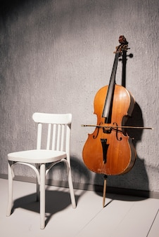 Old battered cello and chair standing near a gray textured wall at school or practice room.