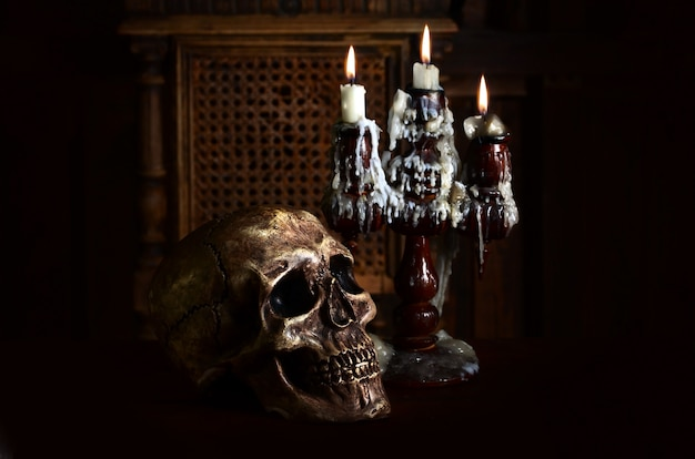 Old battered skull lies with an antique wooden candlestick