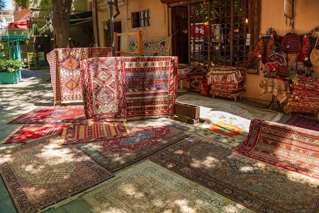 Старые красивые украшенные ковры на уличном рынке в тбилиси. ковры на уличном рынке тбилиси.