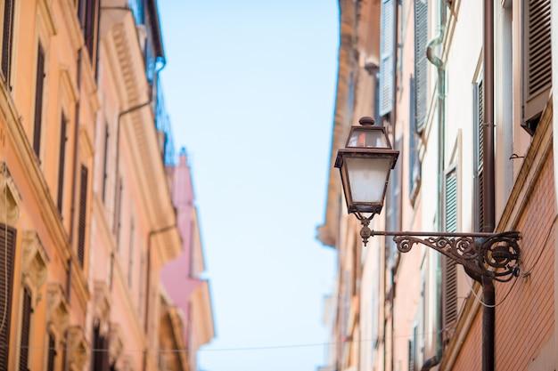 Старые красивые пустые улицы в риме, италии. крупный план уличного фонаря в таунхаусе
