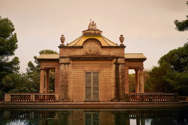 Старое красивое здание парка, отражающееся в пруду