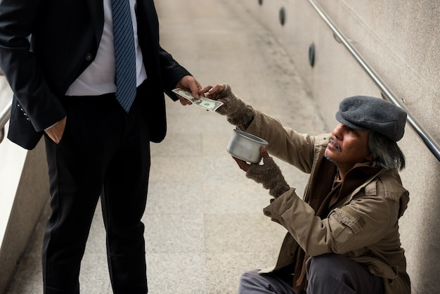 Old beggar or homeless man grab 1 dollar bill money by kind business man at city walk in urban town in winter. poverty and social issue concept. give, donate, help with sympathy.