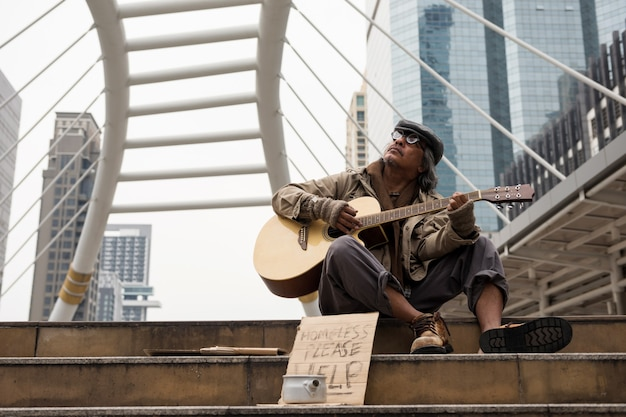 Old beggar or homeless man singing and playing folk song guitar on stair of modern city with donate bowl, paper cardboard with help text to ask for doanation. poverty in town at winter.