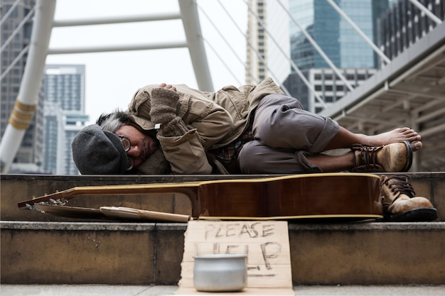 Old beggar or homeless man sleeping and feeling cold on stair of modern city