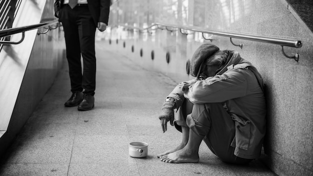 Old beggar or pity homeless dirty man sit and head down on footpath walk of modern city while businessman look and him. poverty and social issue concept. black and white color process.