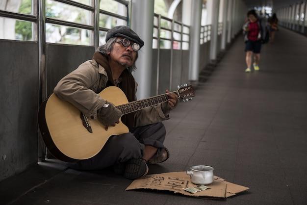 Old beggar play guitar to beg money