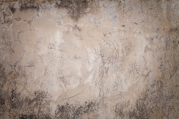 Old beige wall covered with uneven plaster. texture of vintage shabby sand brick surface background