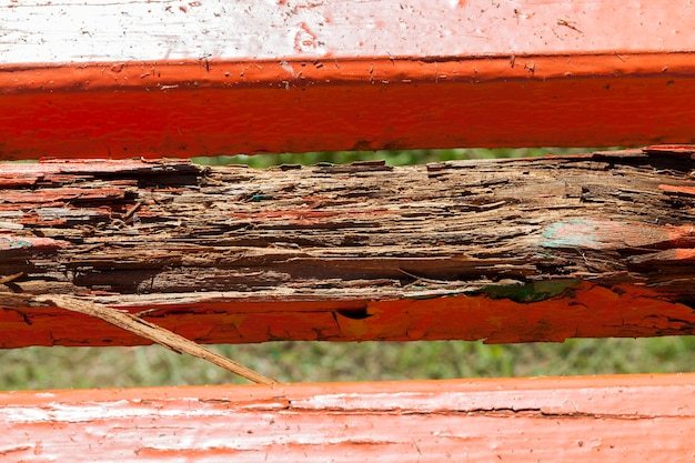 The old bench with a rotten part of the board is painted red