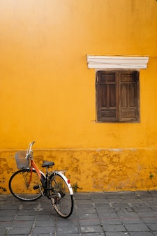 An old bicycle against a yellow wall with a wooden window in the old city of hoi an. place for the label.vietnam.