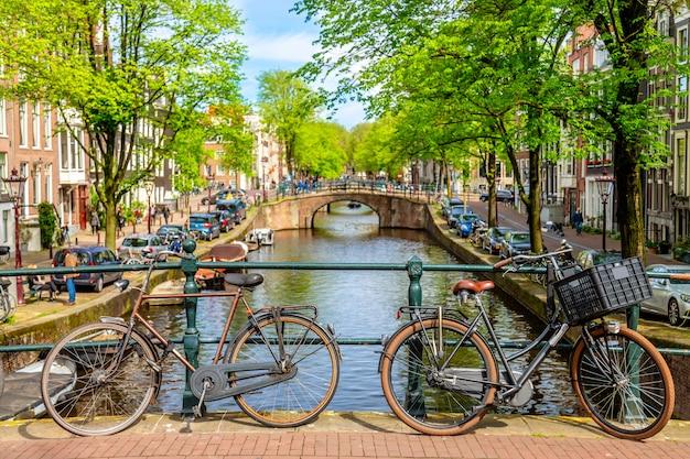 夏の晴れた日の間に運河に対してオランダのアムステルダムの橋の上の古い自転車。