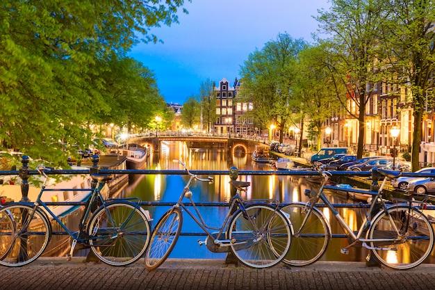 夏の夕暮れ時の運河に対するオランダ、アムステルダムの橋の上の古い自転車。