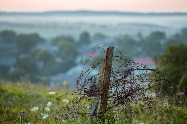 오래 된 큰 철 녹슨 안개, 안개 낀 빛 하늘에 잔디 피 언덕에 정원 울타리 깨진 코일.