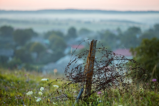 Old big barbed wire coiled on rusty pole, broken garden fence on grassy blooming hill on misty light sky.
