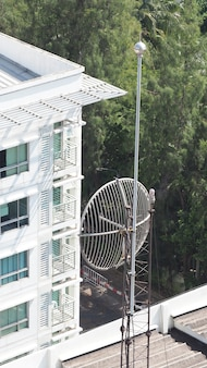 Old big telecommunication satellite dish on roof top of building.