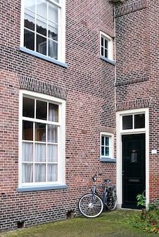 赤れんが造りの壁の家のドアの近くに古い自転車が立っています
