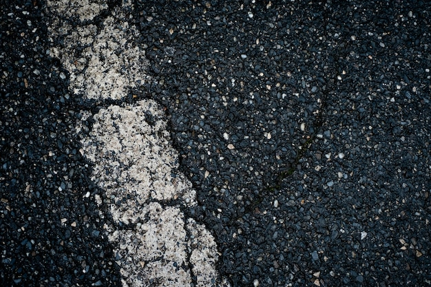 Old black asphalt with white stripe and cracks background