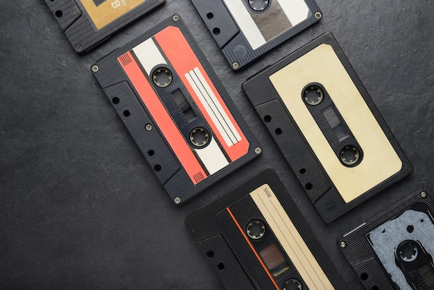 Old black audio tape compact cassettes on black slate background