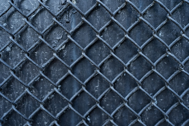 Old black metal background covered with wire mesh grille. metal texture