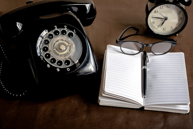 Old black objects on brown imitation leather .old black telephone and black clock and black glasses and black pen and black note , vintage object