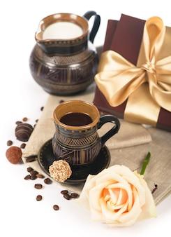 Старая черная керамика, кофейные зерна, конфеты и чашка напитка