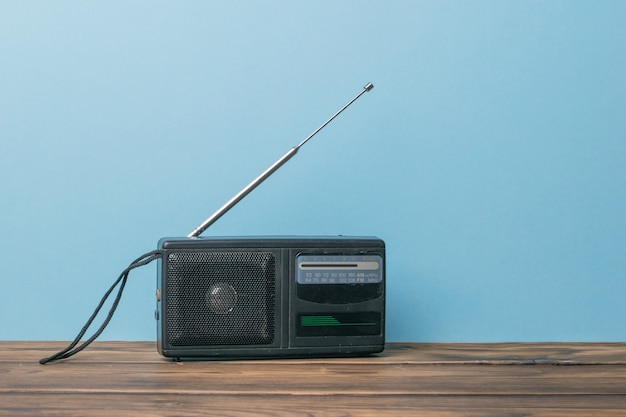 An old black radio on a wooden table on a blue background.