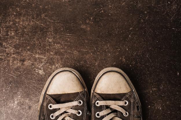 Старые черные кроссовки на темном фоне мрамора. обувь для активного отдыха