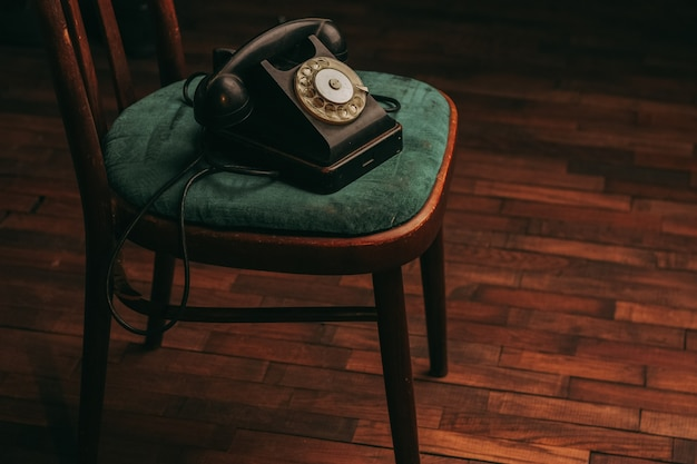 Old black telephone on chair