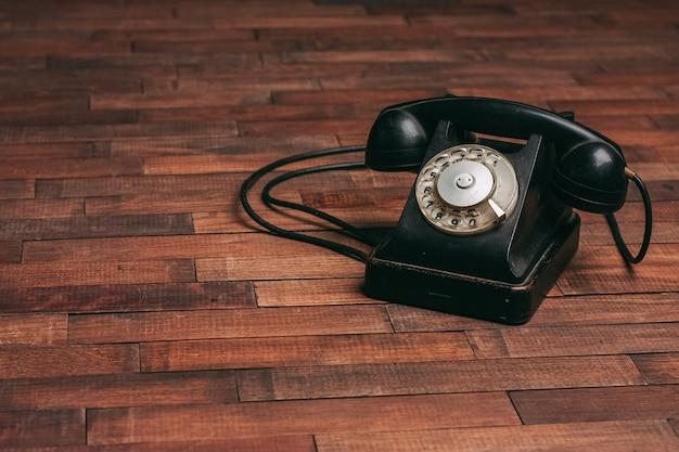 Старый черный телефон на полу