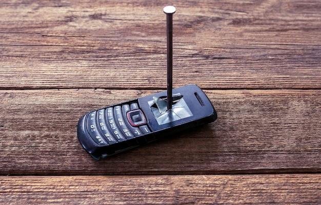 Старый черный телефон с кнопками, прибитыми к деревянному фону