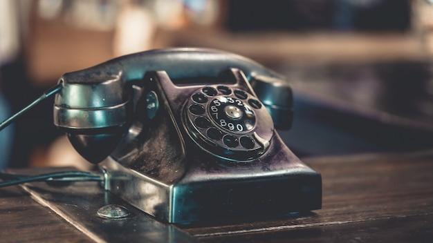 Old black telephone on wooden desk