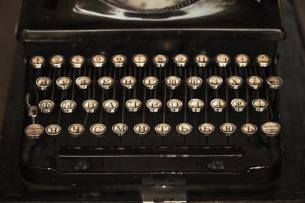 Старая черная пишущая машинка с бумагой стоит на столе