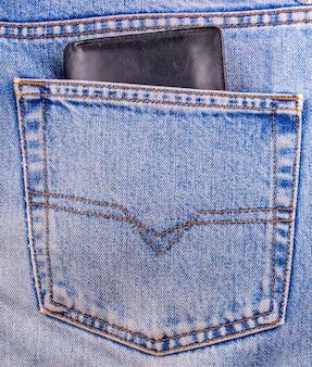 Старый черный кошелек в заднем кармане джинсов