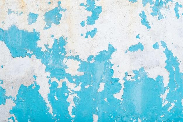古い空白の青いグランジが破れた壁を引き裂いた。しわくちゃの青い絵の背景。テキスト用の壁の空きスペース。