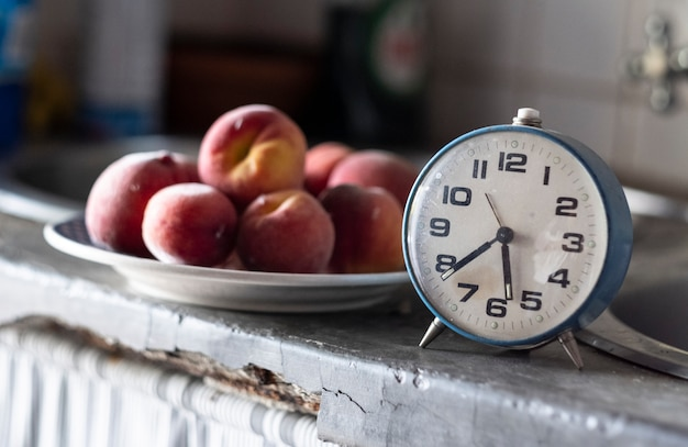 Old blue clock in front of a plate of plums marking the time for a snack