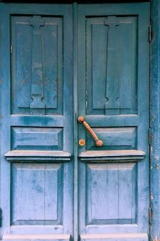 廃墟の古代の家の真鍮のハンドルが付いている古い青いドア。閉じる。屋外。