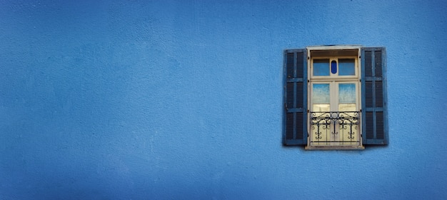 Old blue painted windows on concrete wall. banner with copy space. pop art concept, greek style window