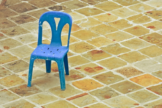 Old blue plastic chair on the brick floor