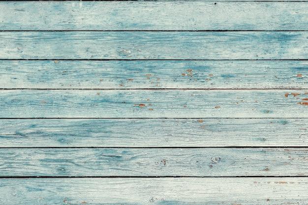 ひびの入ったカラーペイントと古い青いぼろぼろの木板