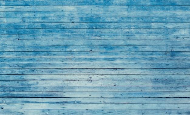 ひびの入った色の塗料で古い青いぼろぼろの木製の板