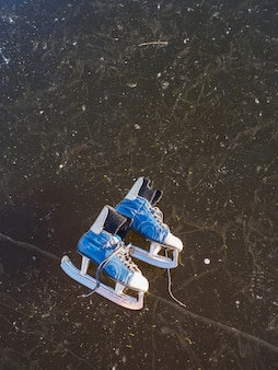 Old blue skates lie on the ice of a frozen lake in the early sunny morning in winter