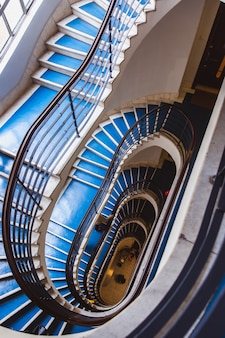 Old blue spiral staircase, spiral stairway inside an old house in budapest, hungary.