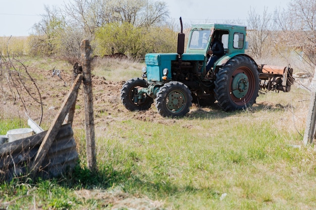 An old blue tractor plows a field and cultivates the soil agriculture