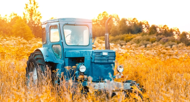 Old blue tractor on the tall grass field