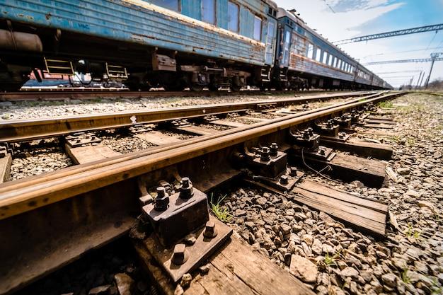 Старый синий вагон на рельсах крупным планом деревянные шпалы или шпалы