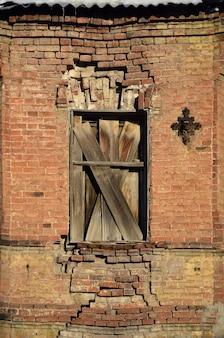 Old boarded window in brick wall