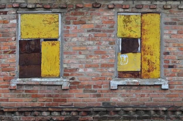 Old boarded windows in brick wall