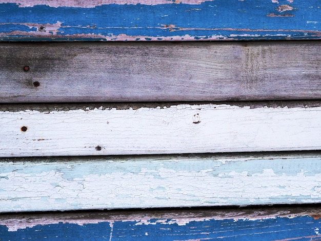 Old boards are painted with different colors of blue, white, paint peels off