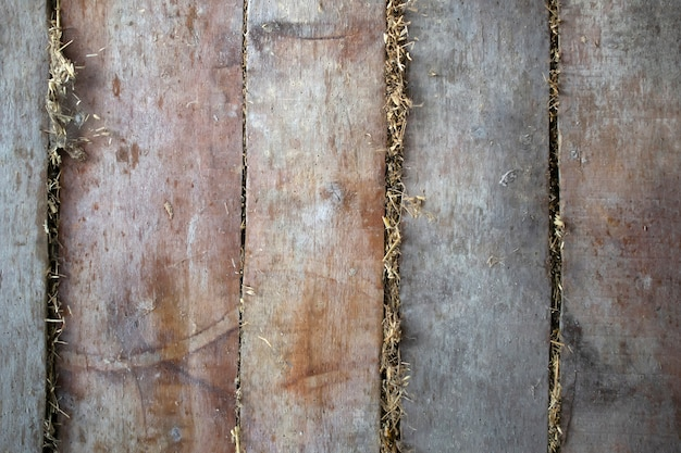 Old boards wall, ceiling, floor background texture with hay from the back