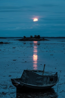 赤い月の下で干潮時の古いボート
