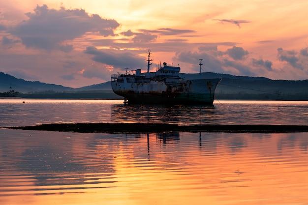 プーケットタイの海の美しい日の出の古いボート